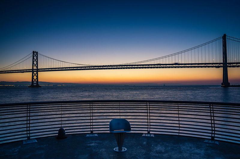 Bay bridge against clear sky at sunrise
