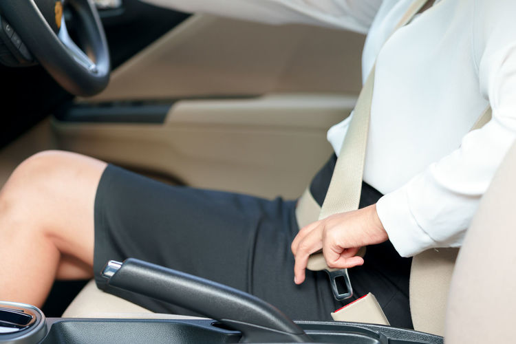 Midsection of businesswoman fastening seat belt in car