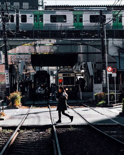 Man walking on railroad tracks in city