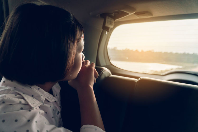 Girl looking through window while sitting in car