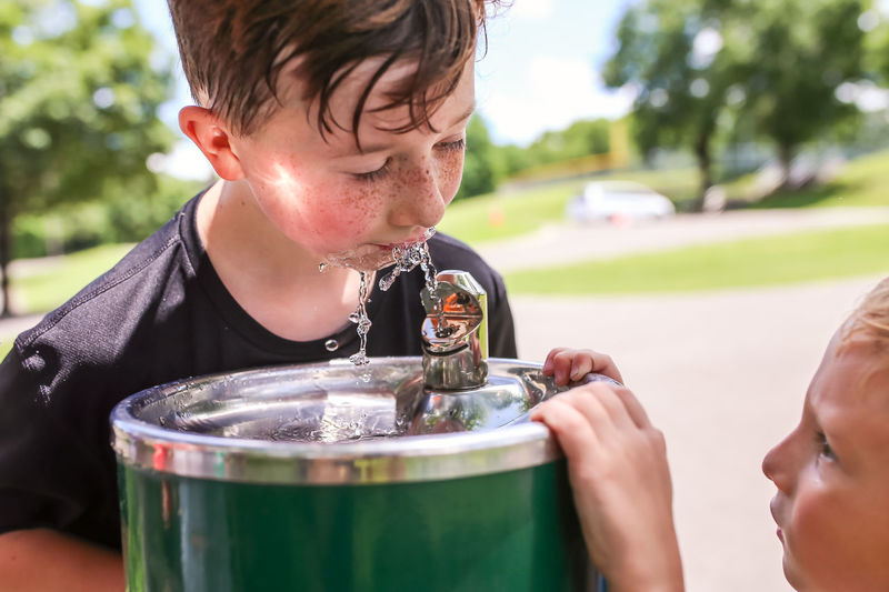 Close-up of boy drinking water from fountain while brother looking