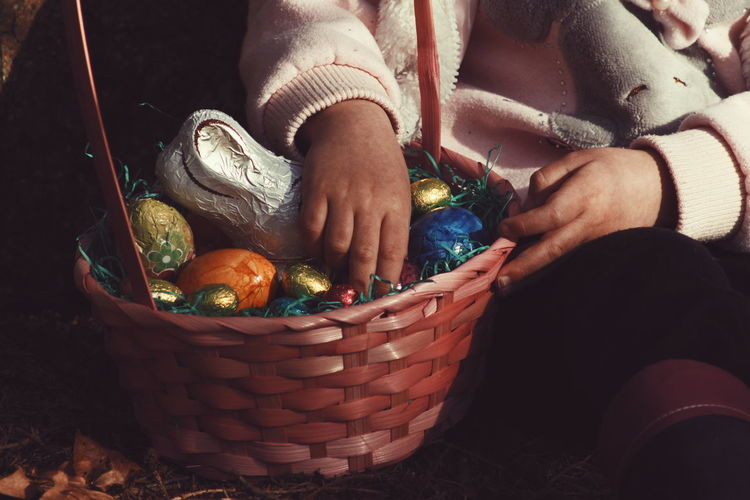 Midsection of person holding easter eggs in basket