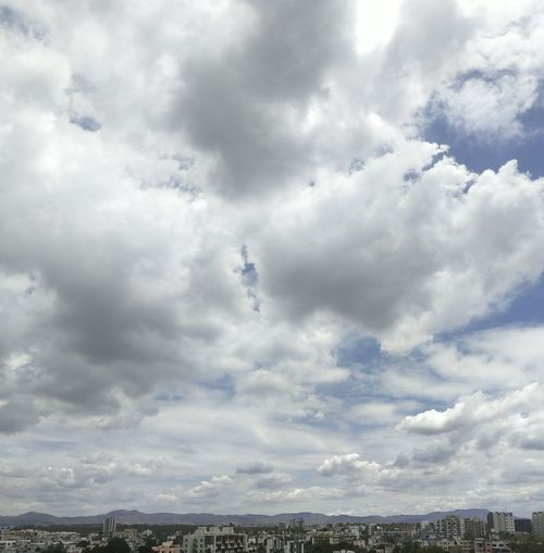 Low angle view of cloudy sky over city