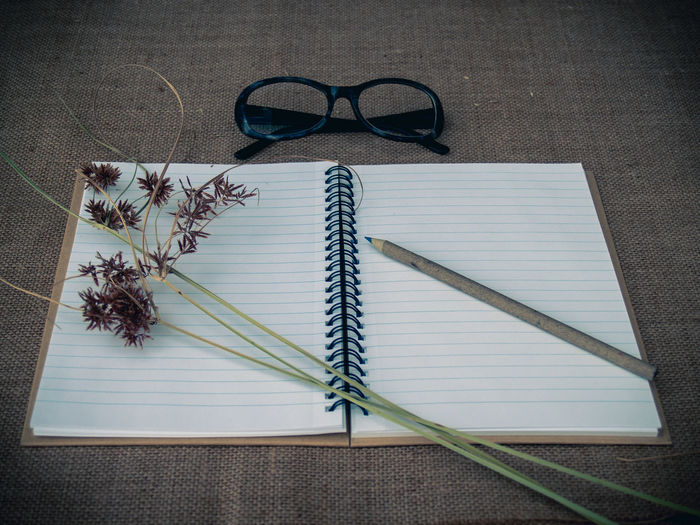 High angle view of pencil and open book with eyeglasses on burlap
