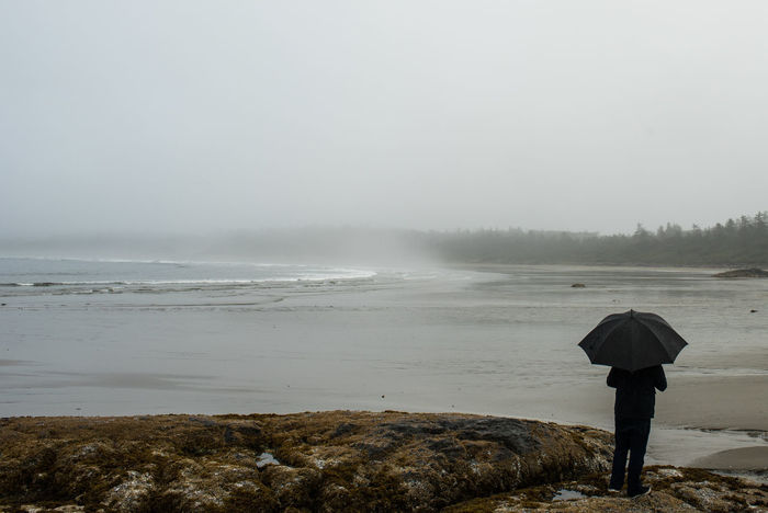 A person looks out over the beach on a foggy morning in Tofino, British Columbia. Beach Beauty In Nature British Columbia Day Foggy Mist Nature Ocean One Person Outdoors Pacific Northwest  Pacific Rim People PNW Protection Real People Scenics Sea Sky Tranquility Under Water Weather West Coast Wet