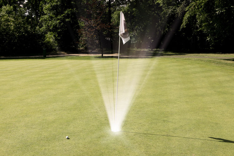 Flag Amidst Light Beam At Golf Course