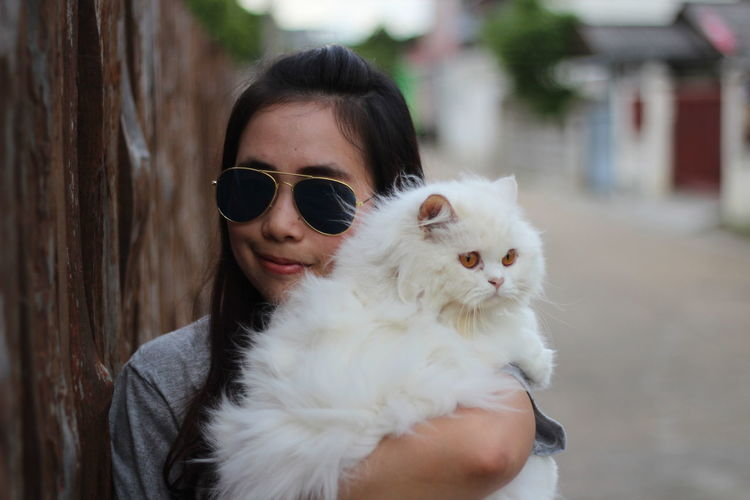 Young woman holding white cat