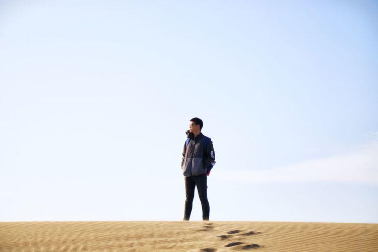 Full length of man standing on sand dune against sky
