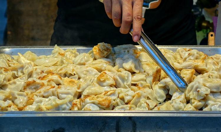 An outdoor vendor sells fried dumplings or pot-stickers Chinese Dumplings Chinese Food Dumplings Food Food And Drink Fried Human Hand Jiaozi Pot Stickers Snack Food Street Food Taiwan Food Tongs