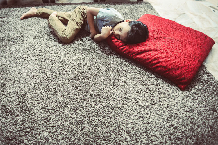 High Angle View Of Boy Relaxing On Rug At Home