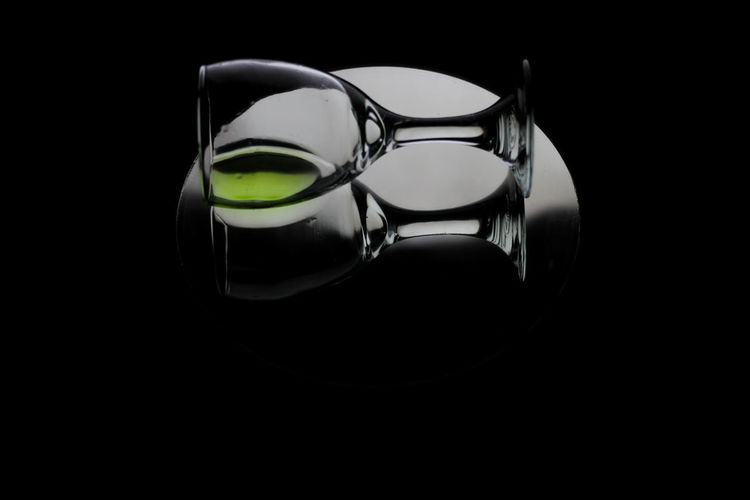 Close-up of glasses on table against black background