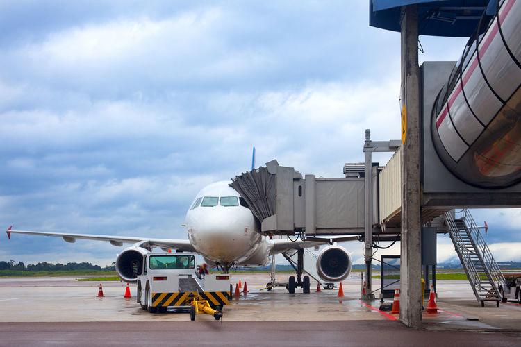 Airplane at airport runway against sky