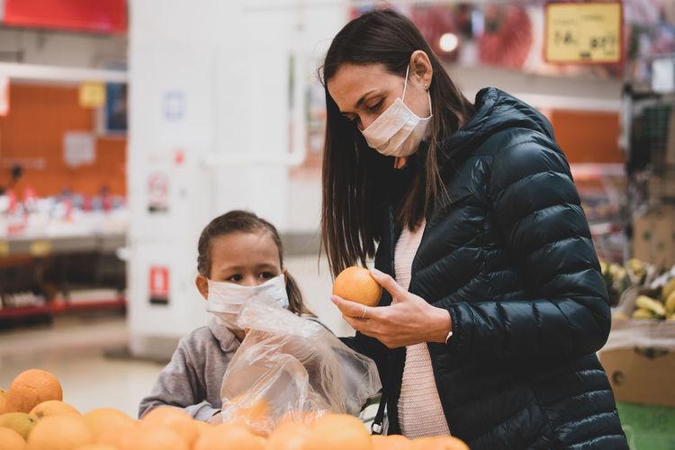 Woman wearing mask choosing orange at supermarket