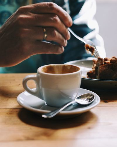 Midsection of man eating cake while having coffee