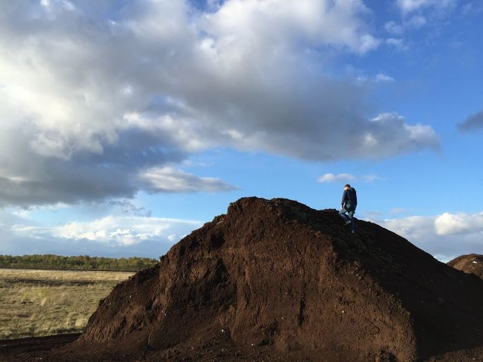 Low angle view of a man on paet rock against sky