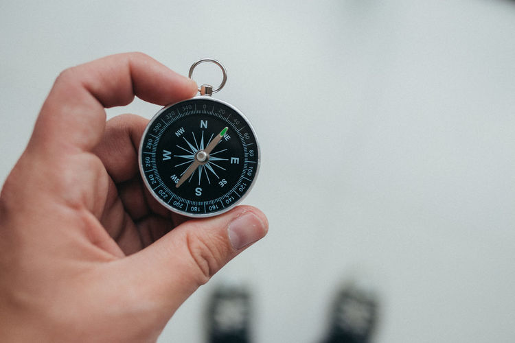 Cropped hand of person holding navigational compass