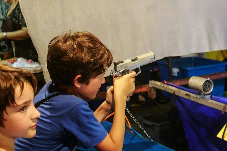 Side view of boy playing with toy gun