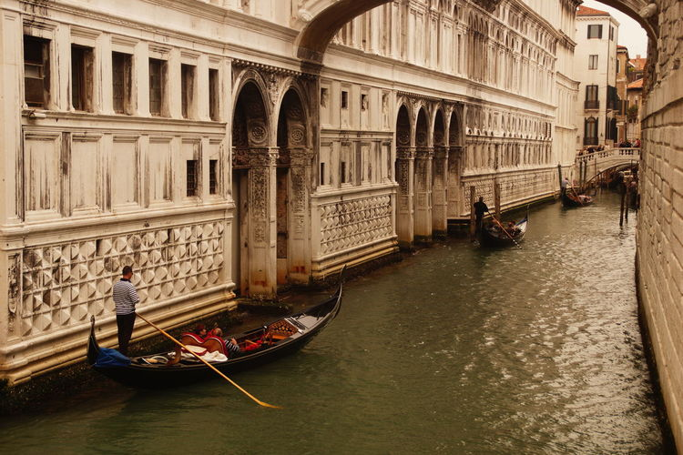 Man standing on gondola by building at grand canal in city