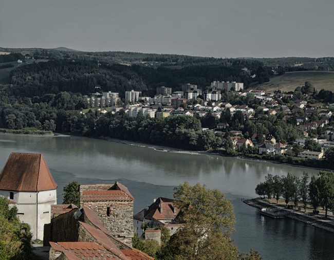 High angle view of townscape by lake against sky