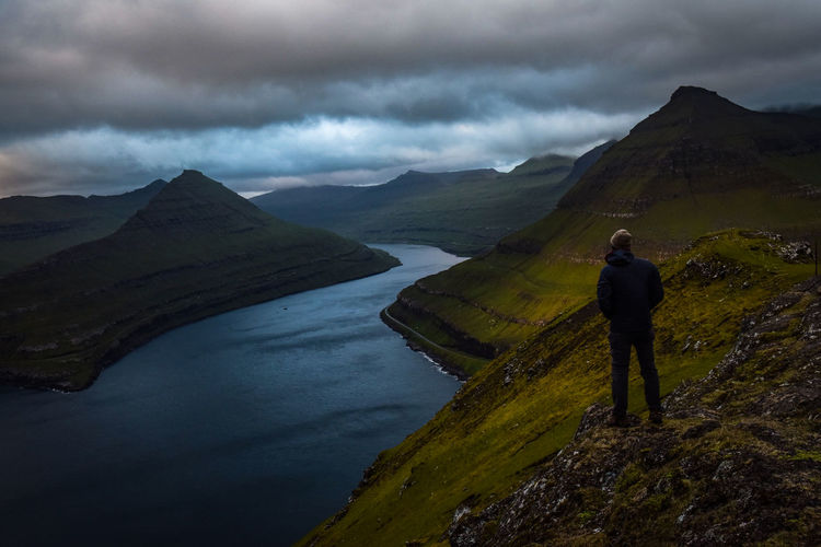 Hiker standing on mountain against cloudy sky during sunset