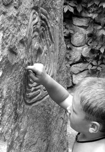 High angle view of boy carving on rock