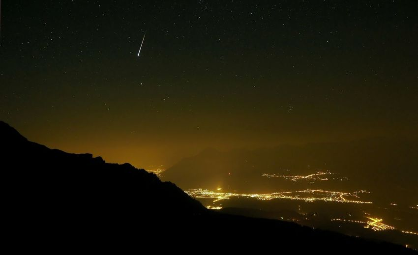 Illuminated residential district against meteor and stars in sky at night