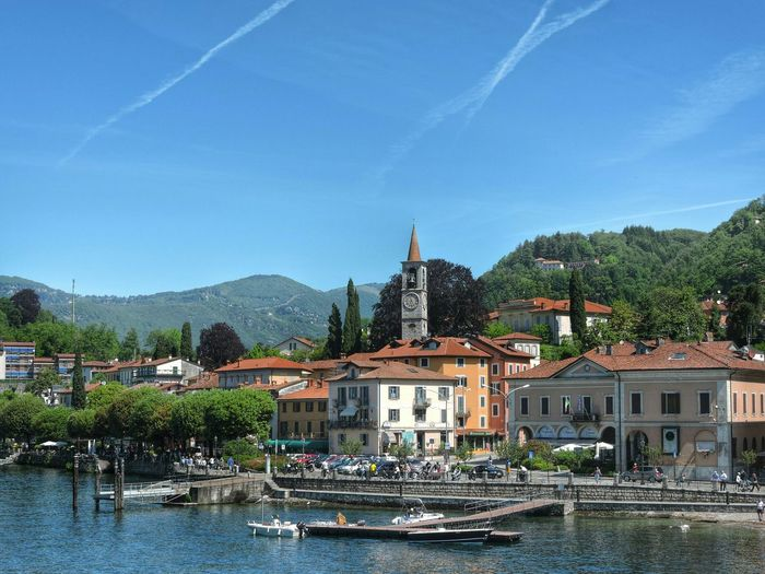 River in front of houses against blue sky at laveno-mombello