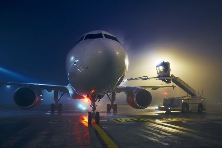 Airplane on airport runway at night