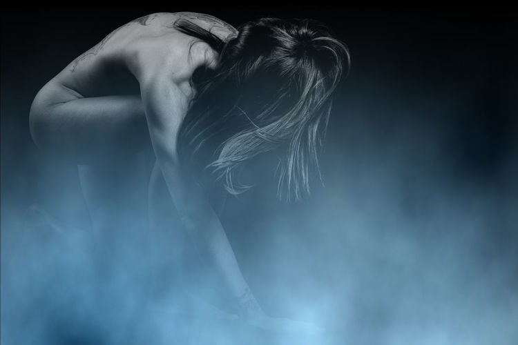Naked woman amidst smoke against black background
