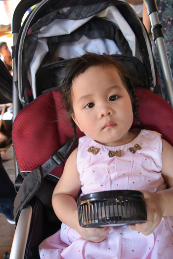 Portrait of baby girl with toy fan on stroller