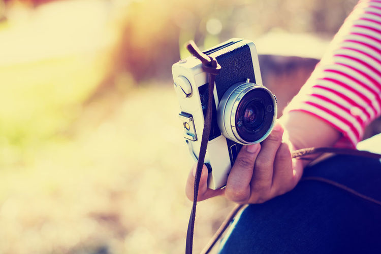 Cropped hand of woman holding camera