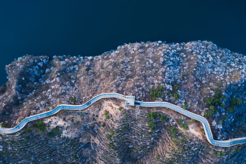 Aerial view of road on land against sea