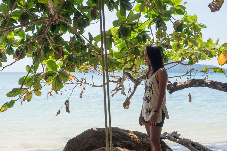 Full length of young woman standing by tree against sea