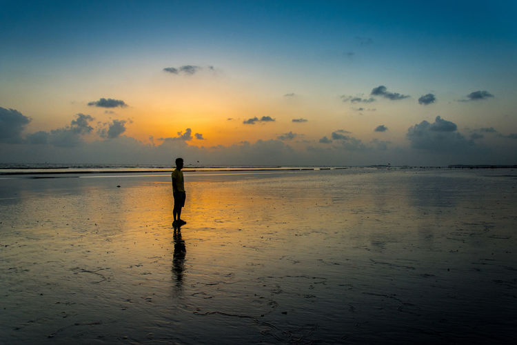 Silhouette person standing on beach against sky during sunset