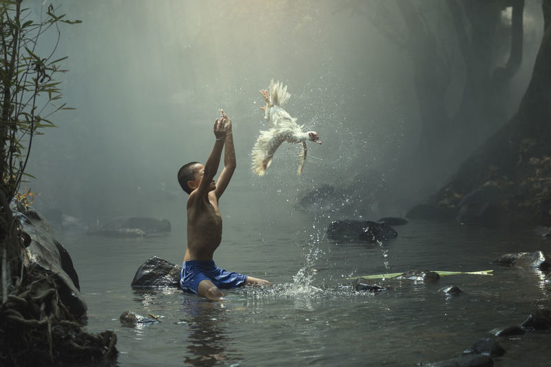 Shirtless boy with arms raised looking at bird flying while sitting on rock in river