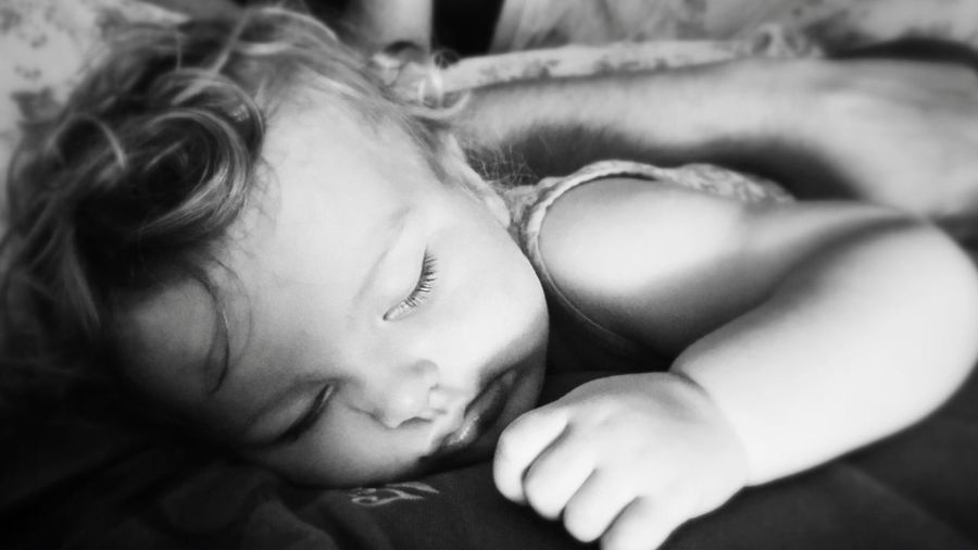 Close-Up Of Baby Girl Sleeping With Father At Home