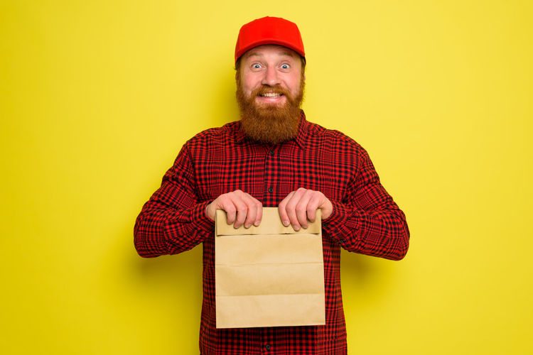 Portrait of man holding hat against yellow background