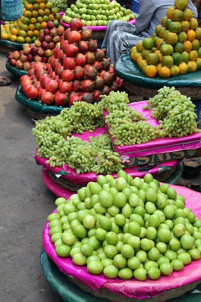Street trader sell fruits outdoor on February 11, 2014 in Kolkata India. Apple Assortment Bazaar Buisness Calcutta Citrus  City Customer  Food Fruit Grapes Greengrocery Grocery India Kolkata Market Market Stall Marketplace Pomegranate Sale Seller Shop STAND Street Tangerine
