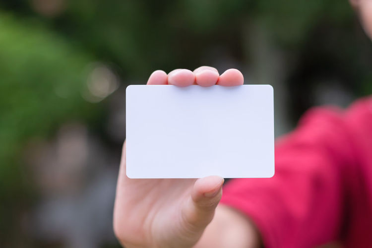 Woman holding white business card on natural bokeh background Business Adult Blank Card Close-up Communication Copy Space Credit Day Empty Finger Focus On Foreground Hand Holding Human Body Part Human Hand Message Mockup One Person Outdoors Personal Perspective Selective Focus Showing White Women