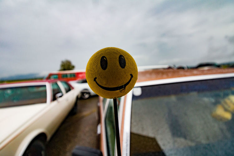 Close-up of smiley face on car against sky
