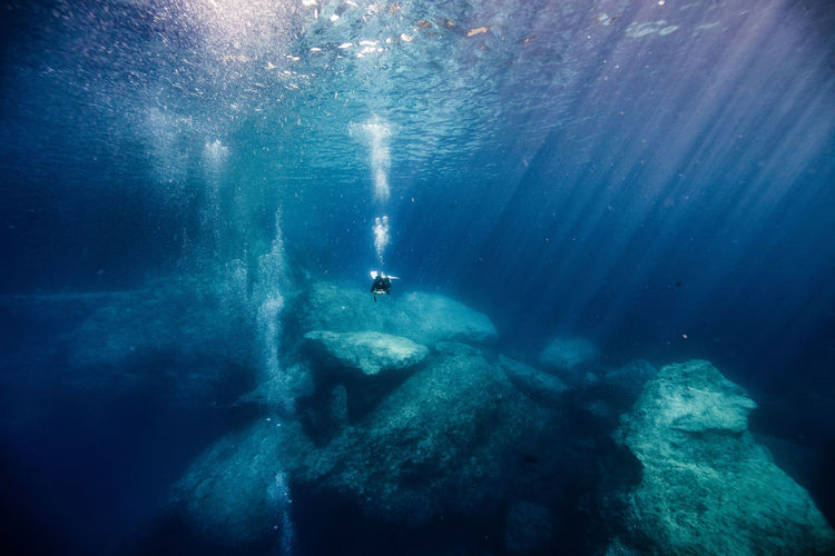 Man Scuba Diving By Rock Formation In Sea At Gozo