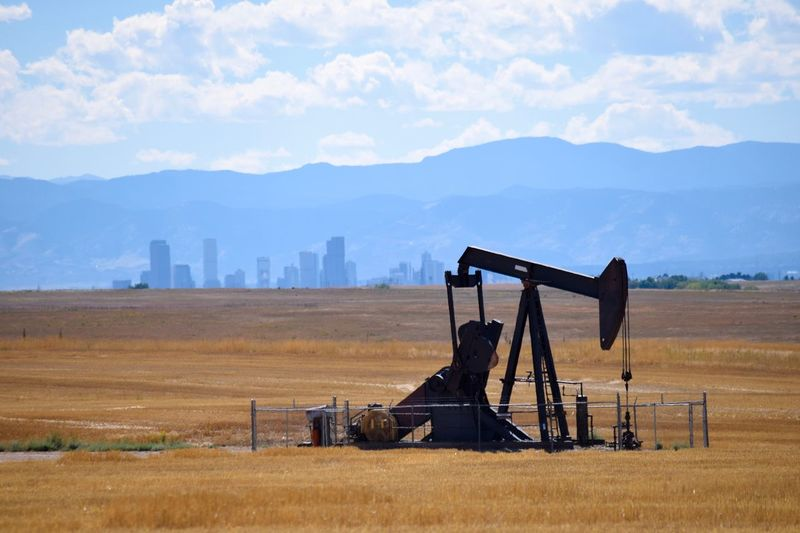 Oil Pump On Field Against Mountains