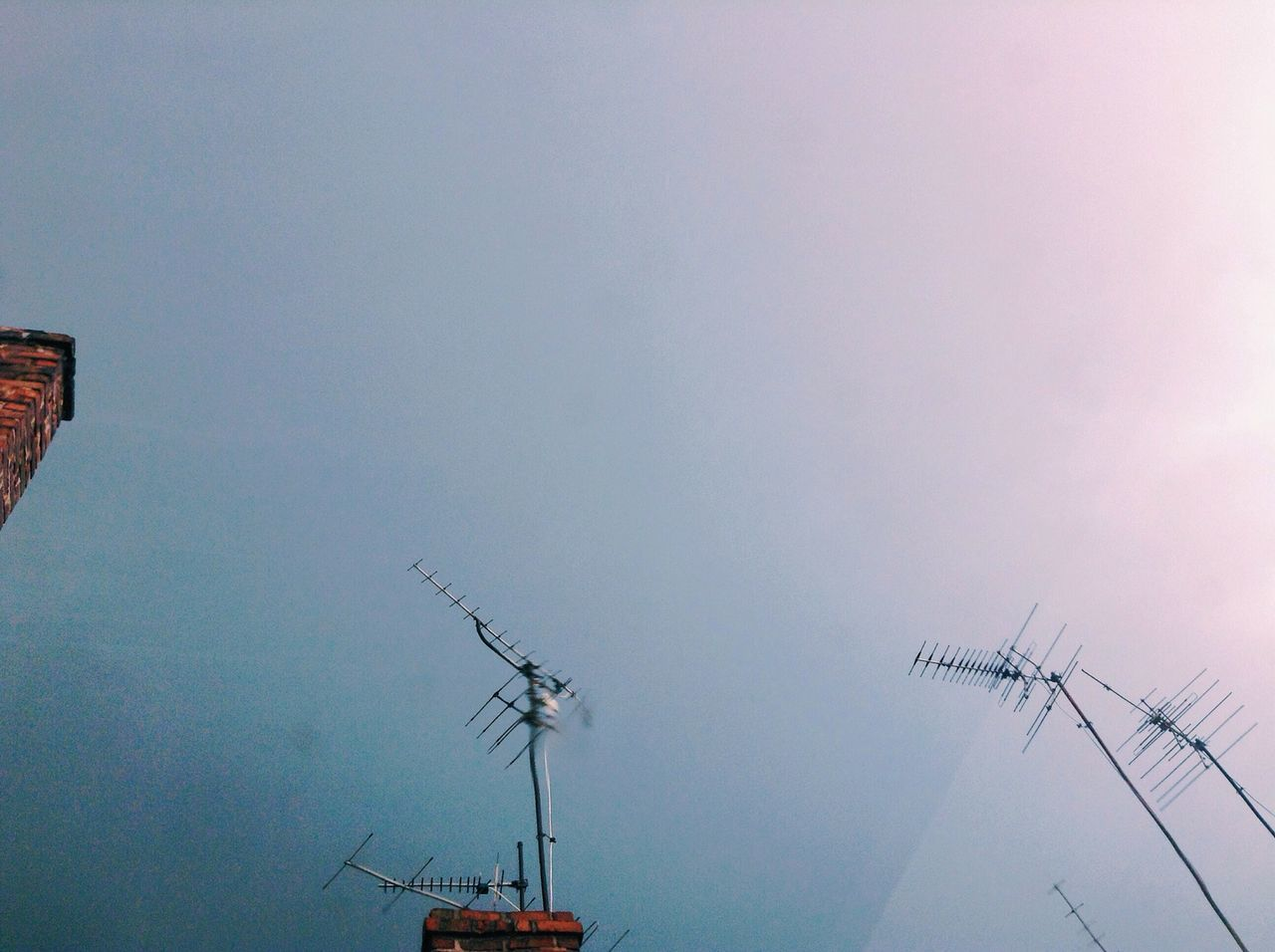Low angle view of television aerials against clear sky