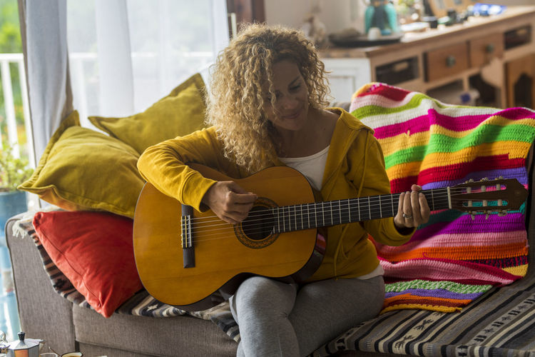Woman playing guitar on sofa at home