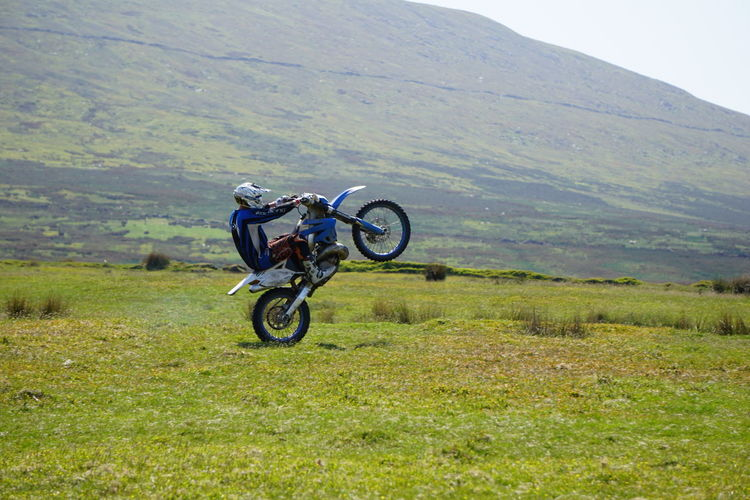 Motocross rider performing stunt on field by mountain