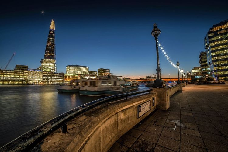 Illuminated Shard London Bridge By Thames River Against Sky At Night