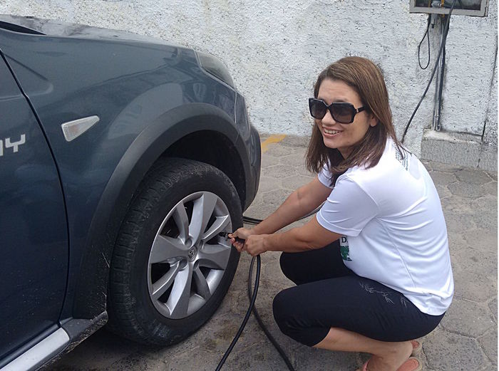 Portrait Of Smiling Woman Inflating Car Tire Using Air Pump