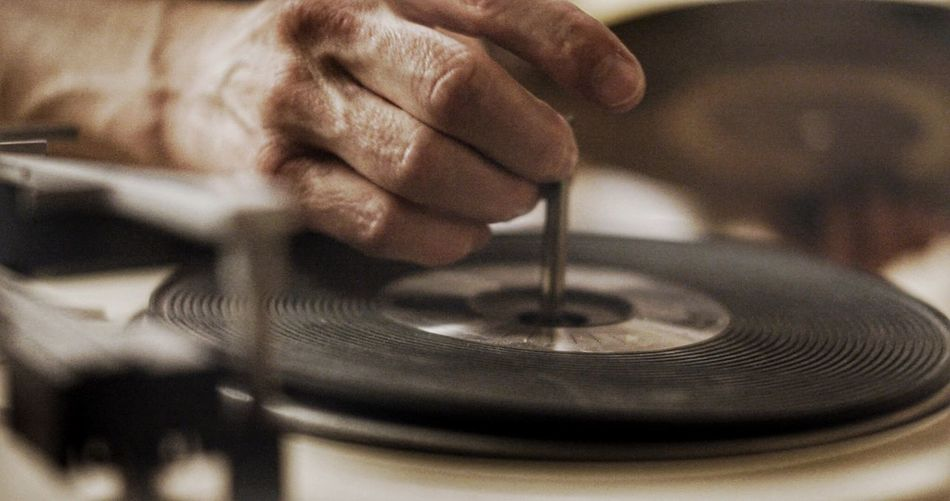 Cropped hand of man on record player needle
