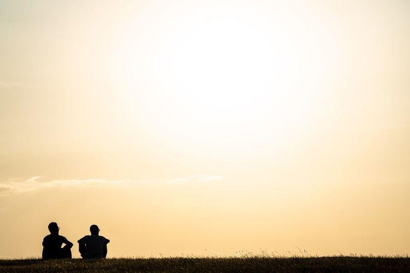 Men on field against sky during sunset