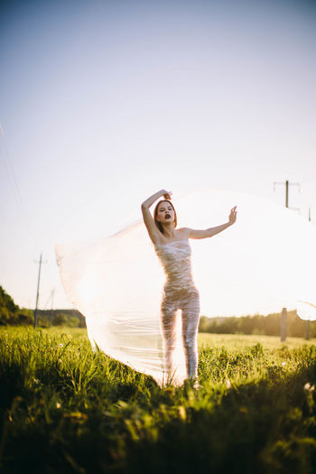 Excitement Human Limb Outdoors Positive Emotion Freedom Women Standing Lifestyles Real People Emotion Full Length Young Adult Nature Limb Happiness Field Leisure Activity Land Arms Raised Plant Sky One Person Grass Human Arm Sunlight